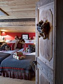 View into cosy chalet bedroom with teddy bears, lamps and Christmas presents