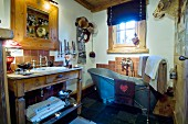 Free-standing zinc bathtub and washstand in rustic bathroom with traditional ambiance