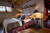 Hunting trophies and festive candlelight in rustic, country-house-style bedroom