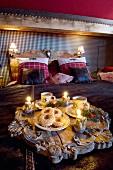 Antikes Holztablett mit Schnitzereien, Porzellan und weihnachtlichen Kerzen auf Bettdecke in Chalet-Schlafzimmer