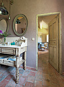 Open door next to antique washstand below oval mirrors
