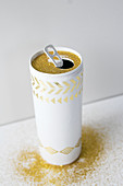 Vase hand-made from can using golden adhesive pattern