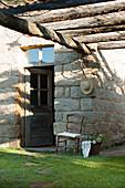 Old wooden chair next to exterior door of stone house below pergola