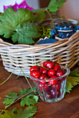 Glass of cherries in front of basket of vine leaves