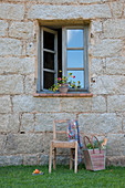 Old chair and shopping basket below open window of stone house