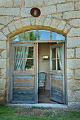 Open double doors with fan light and arched frame leading into old stone house