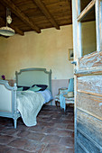 View through open wooden door into Mediterranean bedroom