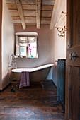 Free-standing bathtub below window in vintage-style bathroom