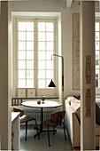 Blick auf runden Tisch und Stehleuchte vor Sprossenfenster