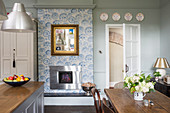 English-style kitchen-dining room with open fireplace and patterned wallpaper on chimneybreast