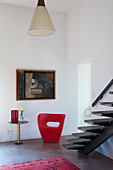 Red designer easy chair at foot of self-supporting staircase