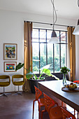 Dining table and orange chairs in front of floor-to-ceiling industrial window