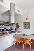 Küche im Industriestil mit Betontisch und bunten Plastikstühlen