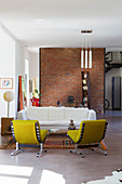 Yellow easy chairs and white sofa in open-plan loft interior