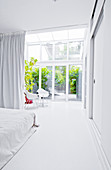 White bedroom with glass wall leading to conservatory