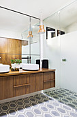 Elegant bathroom with walk-in shower, double walnut vanity, wall mirror and hexagonal floor tiles
