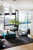 Leather chairs and turquoise ottoman on carpet in lounge with floor-to-ceiling windows