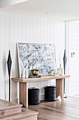 Modern art and vases on wooden console table in the hallway