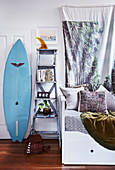 Bed with pillows, next to ladder shelf and surf bed