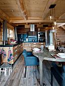Gedeckter Tisch vor der offenen Küche mit Holzfronten im Blockhaus