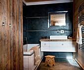 Modern bathroom furnishings and wood panelling in rustic bathroom