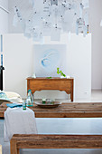 Designer lamp above rustic wooden dining table and bench