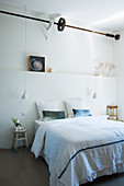 Bed below wall ledge in white bedroom