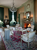 Upholstered chairs and table set for afternoon coffee in historical parlour