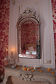 Vintage wall-mounted mirror with etched frame above mantelpiece