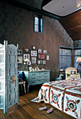 Vintage furniture in bedroom with dark ornate wallpaper