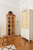 Wooden display case and chest of drawers on parquet floor against panelled walls