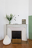 Pleated paper ornament in front of mantelpiece