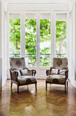 Two armchairs with patterned covers in front of floor-to-ceiling windows
