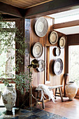 Moroccan plates on a wood-clad wall, including a rustic bench