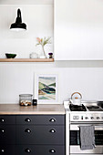 Gas stove next to base cabinet in kitchen with white wood paneling