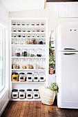 Open white shelf with storage jars next to fridge