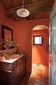 Washstand with wooden base unit in bathroom with terracotta walls and arched open doorway