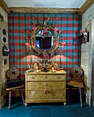 Old chest of drawers and wooden chairs against tartan wall in chalet