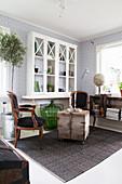 Vitrinenschrank im Wohnzimmer mit Barockstühlen um alte Holzkiste
