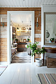View from hallway with rustic board wall into country-house kitchen