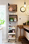 Old wooden crates used as wall-mounted shelving above serving trolley in country-house kitchen