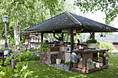 Outdoor kitchen with roof in summery garden