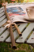 Newspaper in bamboo holders and teacup