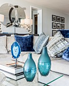 Two blue glass vases and coffee table with glass top in front of sofa with scatter cushions