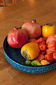Blue bowl with structure surface holding exotic fruit in shades of red