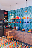 Blue retro wall tiles and colourful crockery in modern kitchen