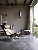 Classic chair with leather upholstery on concrete floor next to glass wall