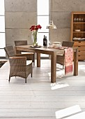 Elegant rattan armchairs and solid-wood table in front of concrete wall with vertical glazed stripes