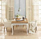 Country-house table and armchairs in front of French windows with vintage shutters