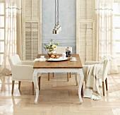 Landhaus-Tisch und Armlehnsessel vor Fenstertüren mit Vintage Fensterläden